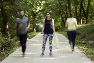 People running and young woman plogging on forest path - ZEDF02623