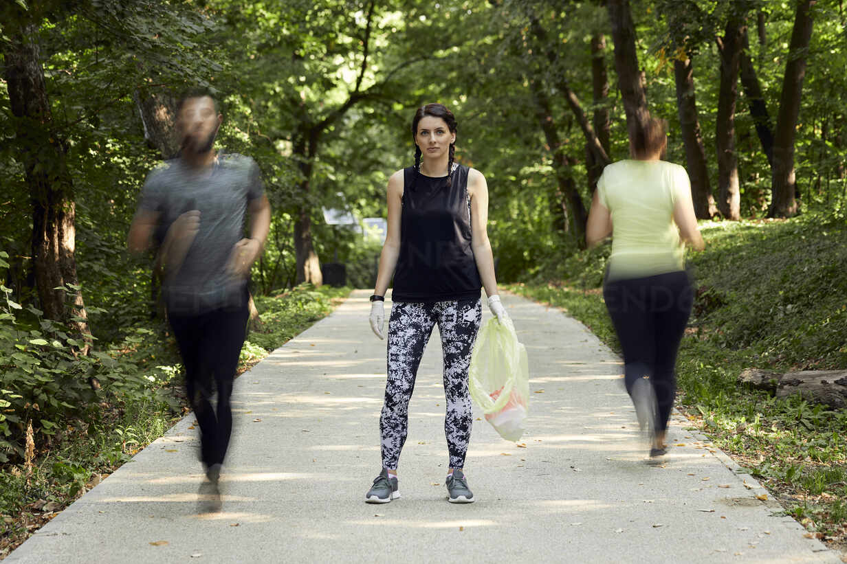 People running and young woman plogging on forest path - ZEDF02623 - Zeljko Dangubic/Westend61