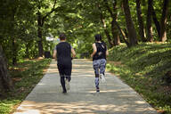 Rear view of sporty couple running on forest path - ZEDF02626