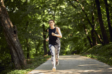 Sporty young woman running on forest path - ZEDF02629