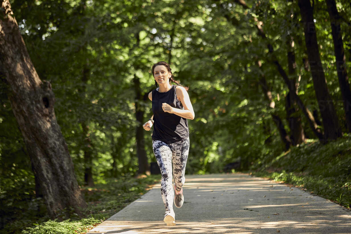 Sporty young woman running on forest path - ZEDF02629 - Zeljko Dangubic/Westend61