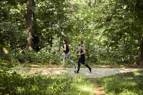 Sporty couple running on forest path - ZEDF02635