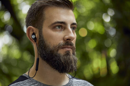 Portrait of sporty man with earphones in forest - ZEDF02641