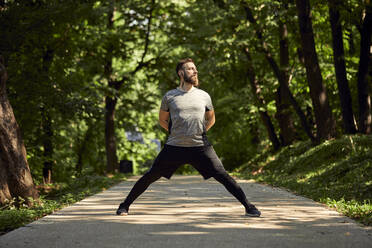 Sporty man stretching on forest path - ZEDF02644