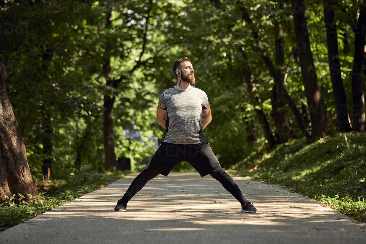 Sporty man stretching on forest path - ZEDF02644 - Zeljko Dangubic/Westend61