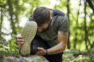 Sporty man stretching in forest - ZEDF02650