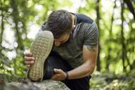 Sporty man stretching in forest - ZEDF02650