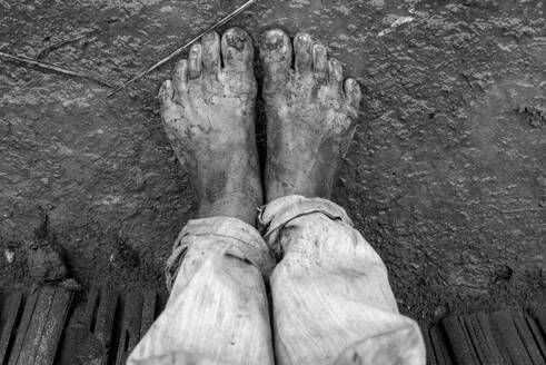 Muddy and barefoot feet of indigenous kid in southern Brazil - CAVF64754