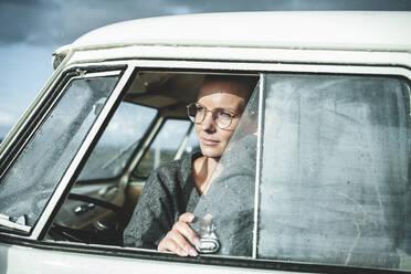 Woman opening window of a van - NAF00130