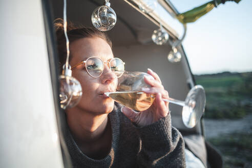 Woman with glass of white wine in van - NAF00133