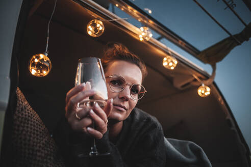 Portrait of woman with glass of white wine in van in the evening - NAF00142