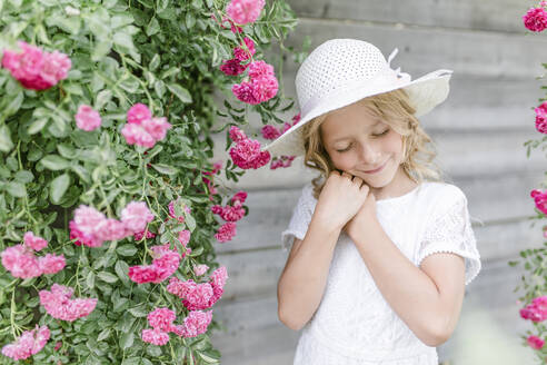 Portrait of smiling girl with closed eyes at rosebush - STBF00423