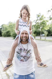 Father carrying playful daughter on his shoulders - STBF00426