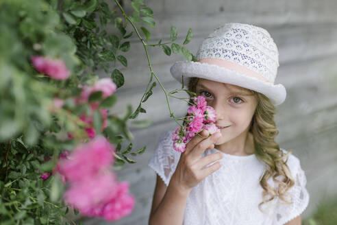 Portrait of girl at rosebush smelling at blossom - STBF00429