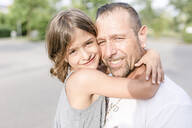 Father and daughter hugging outdoors - STBF00435