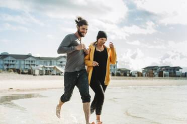 Couple running at the beach in Heiligenhafen - NAF00164