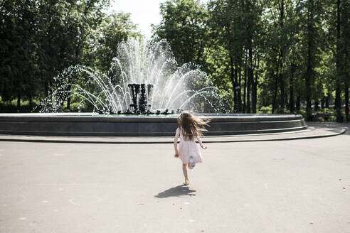 Little girl running towards a fountain - EYAF00539