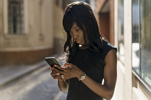 Businesswoman using smartphone in the city - MAUF02930