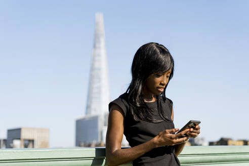 Businesswoman using smartphone in the city - MAUF02936