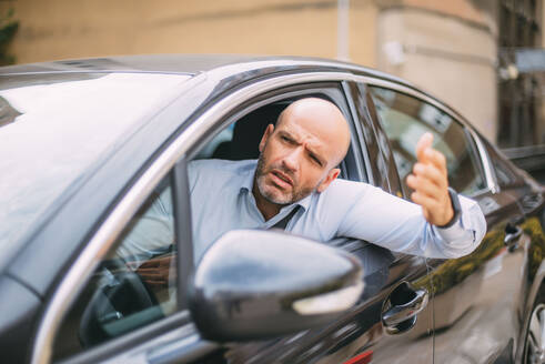 Businessman driving car and looking angry - CJMF00079