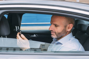 Businessman sitting on a backseat of the car using smartphone - CJMF00085
