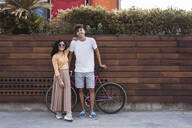 Happy couple with bicycle, standing by wall - RCPF00001