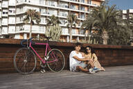 Young couple with bicycle sitting in the city, talking - RCPF00010