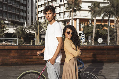 Cool couple with bicycle in the city, standing back to back - RCPF00019