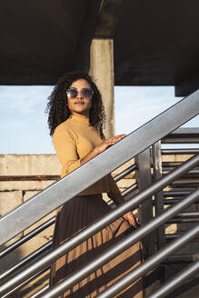 Beautiful woman, wearing sunglasses, standing on stairs - RCPF00022