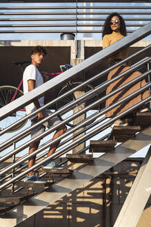 Young couple climbing stairs, carrying bicycle - RCPF00025