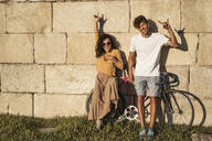 Young couple with bicycle, leaning on stone wall, making hand signs - RCPF00040