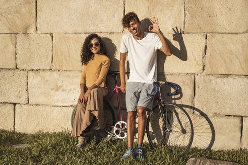 Young couple with bicycle, leaning on stone wall, making hand signs - RCPF00043