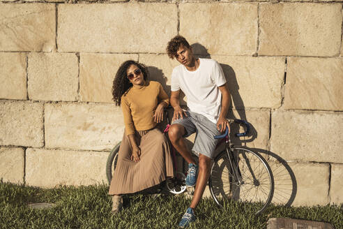 Young couple with bicycle, leaning on stone wall, looking cool - RCPF00046