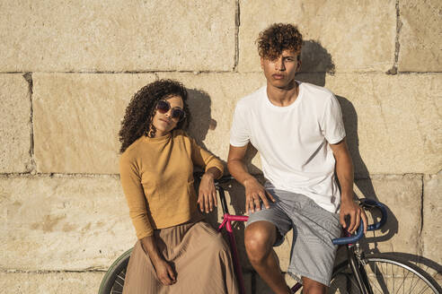 Young couple with bicycle, leaning on stone wall, looking cool - RCPF00049