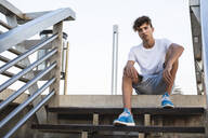 Young man sitting on stairs in the city - RCPF00055