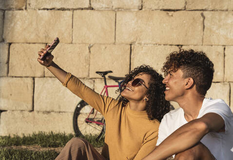 Young couple taking selfies with smartphone, sitting in front of wall - RCPF00058
