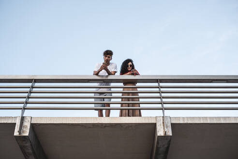 Young couple standing on bridge, using smartphones - RCPF00070