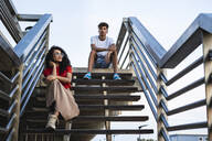 Relaxed couple taking a break, sitting on stairs in the city - RCPF00073