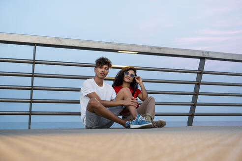 Young couple sitting on bridge by the sea - RCPF00079
