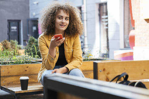Portrait of teenage girl on the phone sitting on bench with coffee to go - VPIF01535