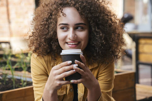 Portrait of smiling teenage girl drinking coffee to go outdoors - VPIF01538
