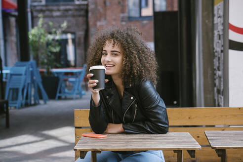 Portrait of smiling teenage girl sitting on bench drinking coffee to go - VPIF01541