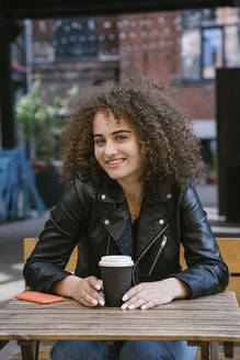 Portrait of smiling teenage girl sitting on bench with coffee to go and mobile phone - VPIF01544