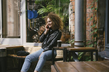 Happy teenage girl on the phone sitting at outdoor cafe with coffee to go - VPIF01550