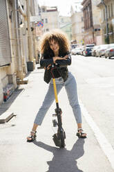 Portrait of smiling teenage girl standing with scooter on pavement - VPIF01571