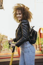 Portrait of smiling teenage girl with backpack and scooter - VPIF01577