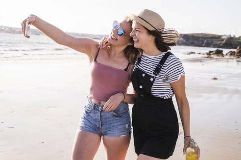 Two girlfriends having fun, walking on the beach, taking smartphone selfies - UUF19030