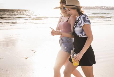 Two girlfriends having fun, walking on the beach, taking smartphone selfies - UUF19033