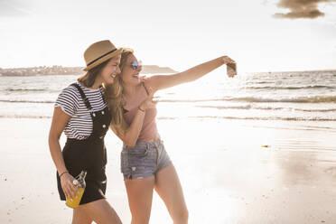 Two girlfriends having fun, walking on the beach, taking smartphone selfies - UUF19036