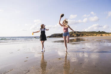 Two girlfriends having fun, running and jumping on the beach - UUF19039